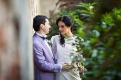 Couples romantiques de nouveaux mariés étreignant près du vieux mur de bâtiment Images stock