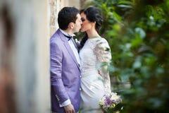 Couples romantiques de nouveaux mariés embrassant près du vieux mur de bâtiment Photo stock