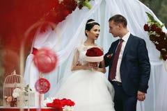 Couples romantiques de nouveaux mariés heureux au bas-côté de mariage avec le decorat rouge Photos stock