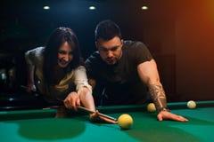 Couples romantiques de sourire jouant le billard dans le club Photographie stock