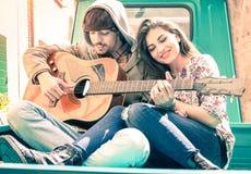 Couples romantiques des amants jouant la guitare sur le minicar de vintage Photographie stock libre de droits