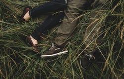 Couples romantiques des jeunes se trouvant sur l'herbe en parc photos libres de droits