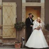 Couples romantiques des nouveaux mariés posant près de la vieille porte dans le St européen Images libres de droits