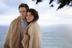 Couples romantiques enveloppés dans la couverture se tenant contre la mer Photos stock