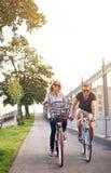 Couples romantiques faisant un cycle tenant des mains Photo stock