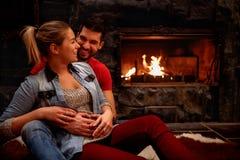 Couples romantiques heureux étreignant à la maison l'avant de la cheminée photos stock