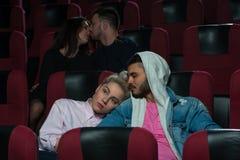 Couples romantiques heureux dans la salle de cinéma Photos libres de droits