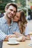 Couples romantiques heureux se reposant au café de trottoir Image stock