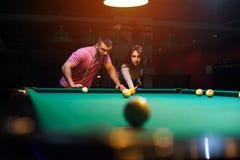 Couples romantiques jouant le billard dans le club foncé Image stock