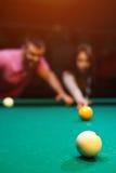 Couples romantiques jouant le billard dans le club foncé Images libres de droits