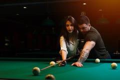 Couples romantiques jouant le billard dans le lub foncé Image stock