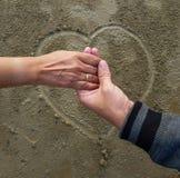 Couples romantiques la date tenant des mains sur le fond de signe de coeur dessiné sur le sable humide de plage image libre de droits