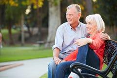 Couples romantiques mûrs se reposant sur le banc de parc ensemble Photos stock