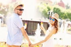 Couples romantiques mangeant de la glace en parc Photographie stock