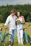 Couples romantiques marchant avec le vieux vélo dans le pré Image libre de droits