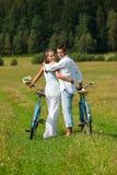 Couples romantiques marchant avec le vieux vélo dans le pré Images stock