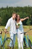 Couples romantiques marchant avec le vieux vélo dans le pré Photos stock