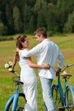 Couples romantiques marchant avec le vieux vélo dans le pré Photos libres de droits