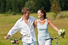 Couples romantiques marchant avec le vieux vélo dans le pré Image stock