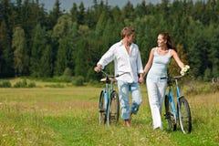 Couples romantiques marchant dans le pré avec le vieux vélo Image stock