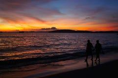 Couples romantiques marchant sur la plage pendant le coucher du soleil Image stock