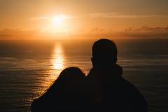 Couples romantiques observant le coucher du soleil dans l'océan Silhouette Photo libre de droits