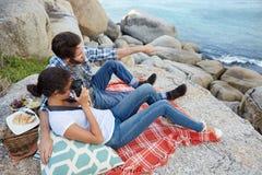 Couples romantiques, pendant un pique-nique sur les roches Photo libre de droits