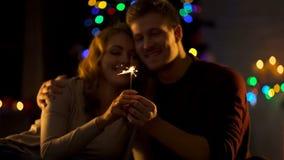 Couples romantiques regardant la lumière de Bengale, faisant le souhait sur Noël, miracle images libres de droits
