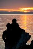 Couples romantiques regardant le coucher du soleil au-dessus de l'eau Photo stock