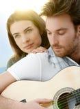 Couples romantiques se reposant jouant le ? extérieur de guitare photographie stock libre de droits