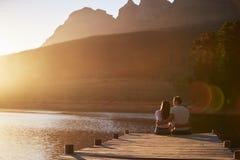 Couples romantiques se reposant sur la jetée en bois par le lac photographie stock
