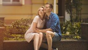 Couples romantiques se reposant sur le banc et examinant l'avenir heureux, sentiments tendres Images stock
