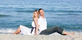 Couples romantiques se reposant sur le sable Photographie stock