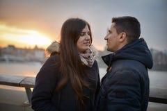 Couples romantiques se reposant sur un pont au coucher du soleil regardant chaque ot Image libre de droits