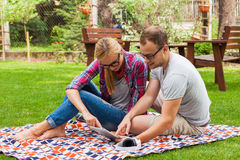 Couples romantiques se reposant sur une couverture avec le PC de comprimé à l'été GR Images stock