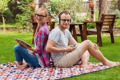 Couples romantiques se reposant sur une couverture avec le PC de comprimé à l'été GR Images libres de droits