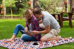 Couples romantiques se reposant sur une couverture avec le PC de comprimé et le p mobile Photos libres de droits
