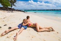 Couples romantiques se trouvant à la plage Photographie stock libre de droits