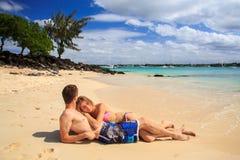 Couples romantiques se trouvant à la plage Photos libres de droits