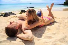 Couples romantiques se trouvant à la plage Photo libre de droits