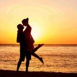 Couples romantiques sur la plage au coucher du soleil coloré sur le fond Photographie stock