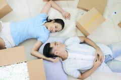 Couples romantiques sur le plancher parmi des boîtes photos libres de droits