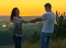 Couples romantiques tenant des mains au coucher du soleil sur le paysage extérieur et beau et le ciel jaune lumineux, concept de  Photos libres de droits