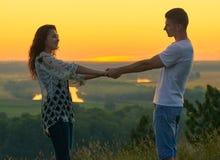 Couples romantiques tenant des mains au coucher du soleil sur le paysage extérieur et beau et le ciel jaune lumineux, concept de  Photographie stock libre de droits