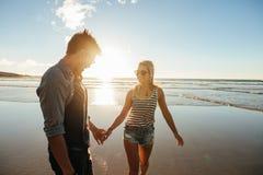 Couples romantiques tenant des mains et marchant sur la plage Image libre de droits