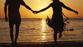 Couples romantiques tenant des mains fonctionnant à la plage sur le coucher du soleil étonnant Ayant l'amusement ensemble aux vac banque de vidéos
