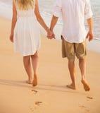 Couples romantiques tenant des mains marchant sur la plage au coucher du soleil Photos libres de droits