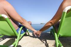 Couples romantiques tenant des mains se reposant sur des chaises de plage Photo stock