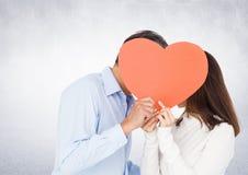 Couples romantiques tenant la forme de coeur et s'embrassant Photographie stock