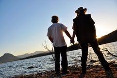 Couples romantiques tenant le bord de coucher du soleil de mains du lac Images stock